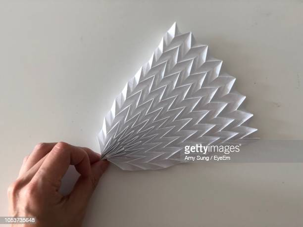 cropped image of hand holding origami art work on wall - origami stock pictures, royalty-free photos & images