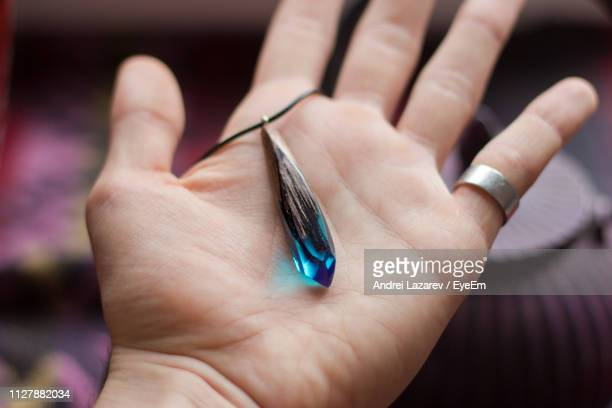 cropped image of hand holding pendant - pendant stock pictures, royalty-free photos & images