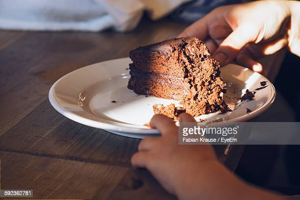 Cropped Image Of Hand Holding Plate With Cake On Table