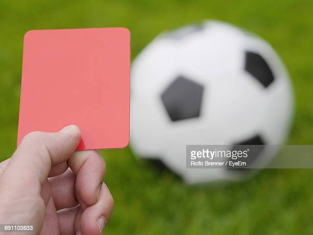 Cropped Image Of Hand Holding Red Card Against Soccer Ball On Field