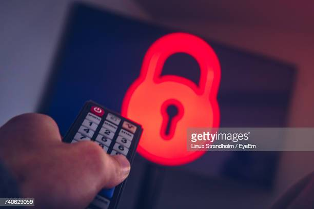 Cropped Image Of Hand Holding Remote Control In Front Of Television Set With Ransomware Icon