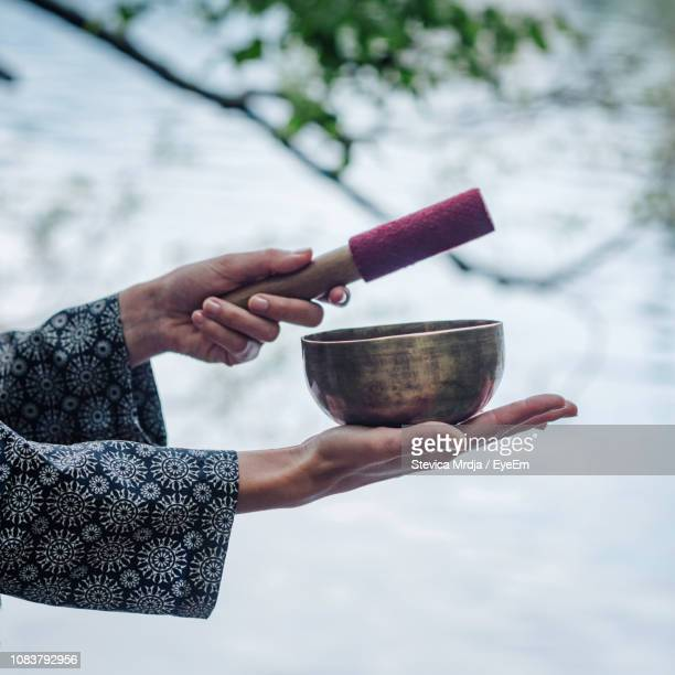 cropped image of hand holding rin gong - gong stock photos and pictures