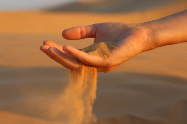 Cropped Image Of Hand Holding Sand In The Desert During Sunset