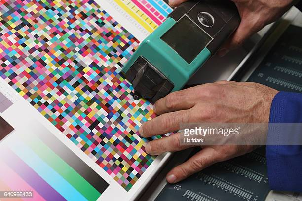 cropped image of hand holding scanner and checking quality of printed paper - printing press stock pictures, royalty-free photos & images