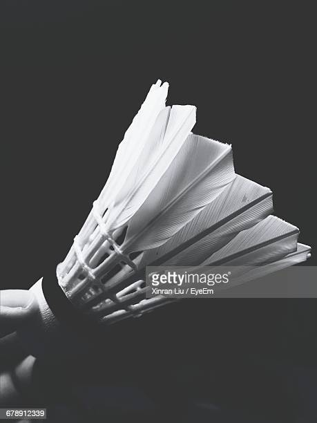 cropped image of hand holding shuttlecock against black background - shuttlecock stock pictures, royalty-free photos & images