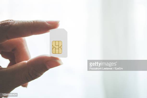 Cropped Image Of Hand Holding Sim Card