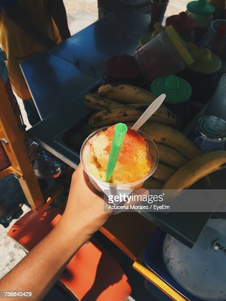 Cropped Image Of Hand Holding Slushie In Disposable Cup At Stall