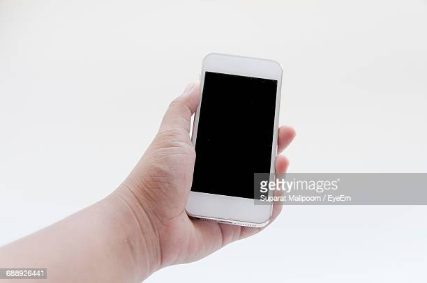 Cropped Image Of Hand Holding Smart Phone Against White Background
