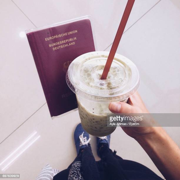 Cropped Image Of Hand Holding Smoothie And Passport