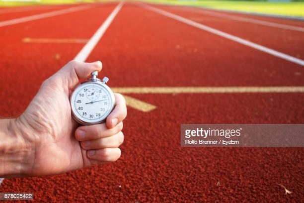 Cropped Image Of Hand Holding Stopwatch Against Running Tracks