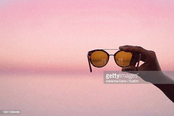 Cropped Image Of Hand Holding Sunglasses Against Pink Wall