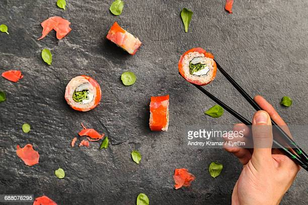 Cropped Image Of Hand Holding Sushi With Chopsticks On Stone Tray