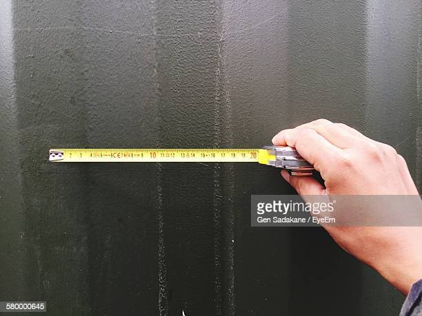 Cropped Image Of Hand Holding Tape Measure Against Wall