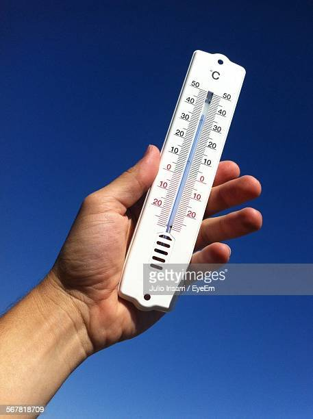 Cropped Image Of Hand Holding Thermometer Against Clear Sky