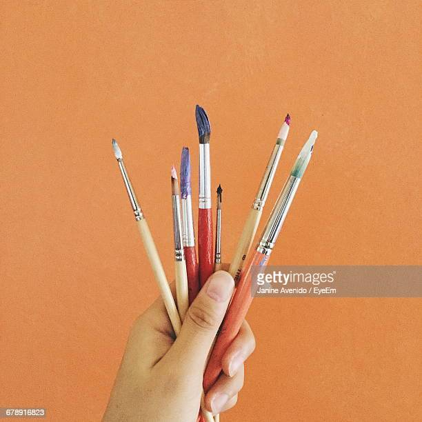 Cropped Image Of Hand Holding Various Paintbrushes Against Orange Background