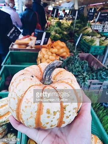 Cropped Image Of Hand Holding Vegetable At Market