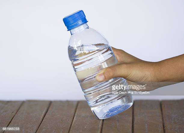 Cropped Image Of Hand Holding Water Bottle Over Table Against Wall