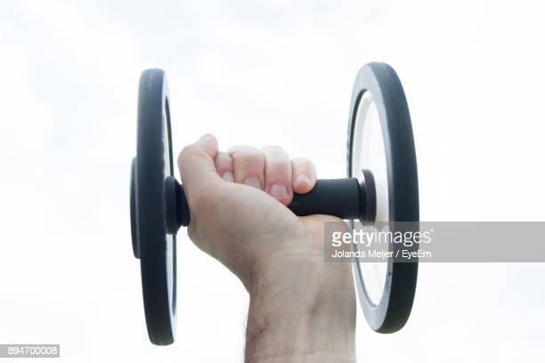 Cropped Image Of Hand Holding Weights Against White Background