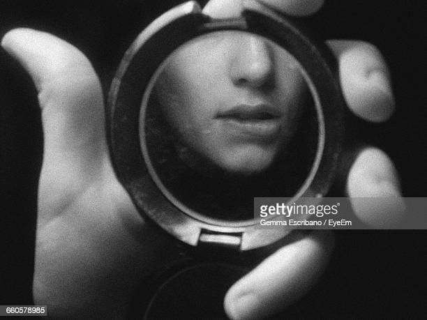 Cropped Image Of Hand Holding With Woman Biting Lip Reflection Against Black Background