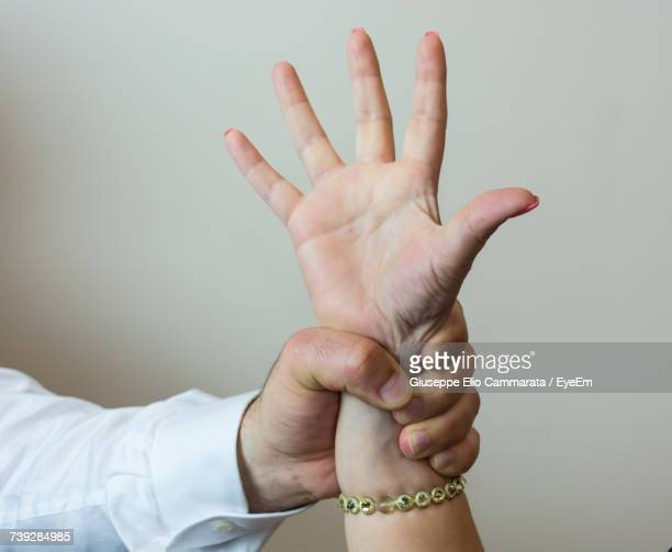 Cropped Image Of Hand Holding Wrist Against Wall