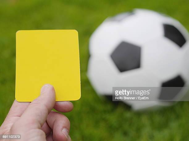 Cropped Image Of Hand Holding Yellow Card Against Soccer Ball On Field