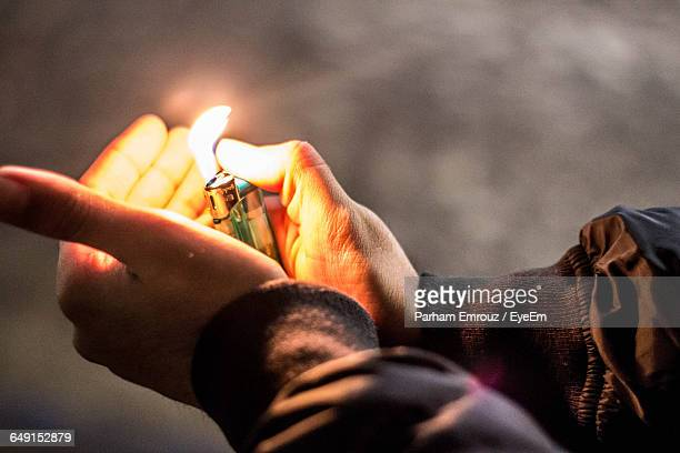 Cropped Image Of Hand Igniting Cigarette Lighter