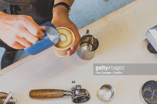Cropped Image Of Hand Making Froth Art In Espresso Coffee At Counter In Cafe