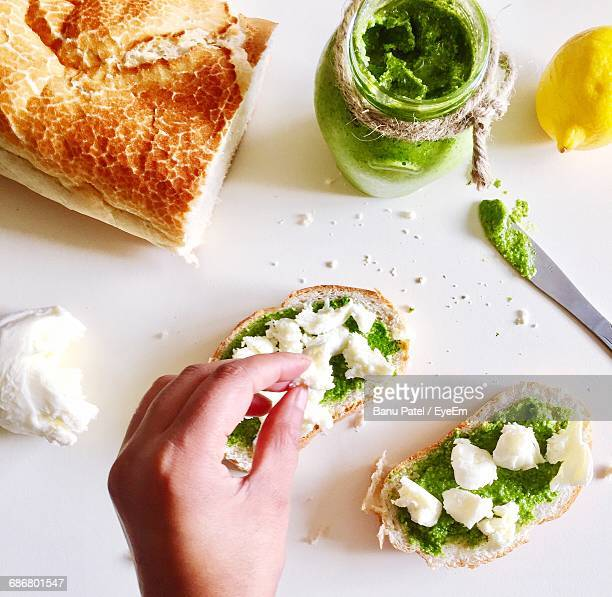 Cropped Image Of Hand Making Sandwich On Table