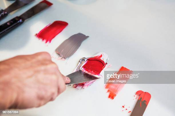 cropped image of hand mixing colors on table at workshop - mixing stock pictures, royalty-free photos & images