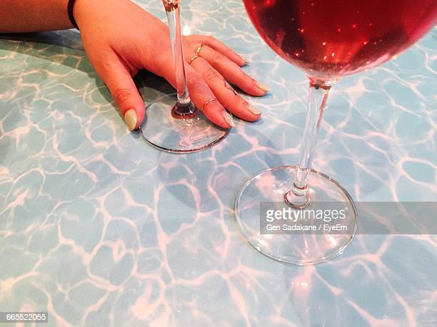 Cropped Image Of Hand On Wineglass At Table