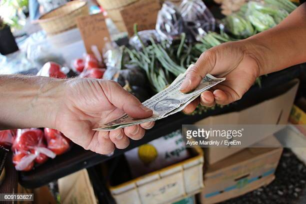 Cropped Image Of Hand Paying Cash To Farmer