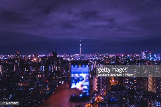 Cropped Image Of Hand Photographing Illuminated Cityscape At Night