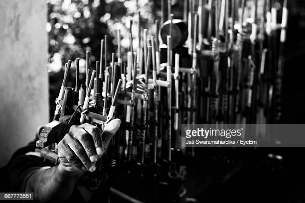 cropped image of hand playing angklung - angklung stock photos and pictures