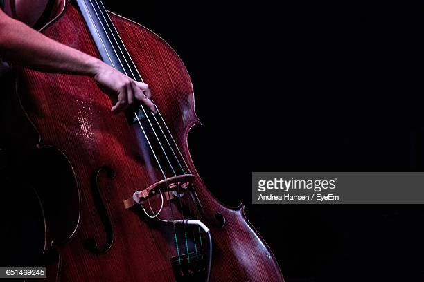 Cropped Image Of Hand Playing Double Bass Against Black Background