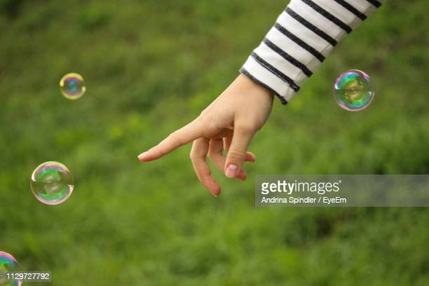Cropped Image Of Hand Pointing At Bubble