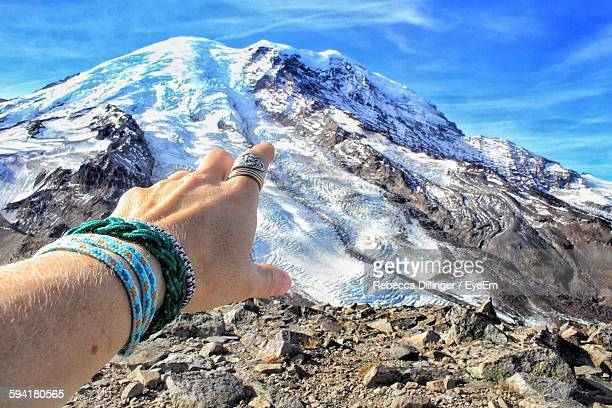 Cropped Image Of Hand Pointing Towards Snowcapped Mountain