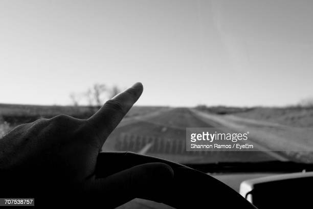 Cropped Image Of Hand Pointing While Driving Car Against Clear Sky