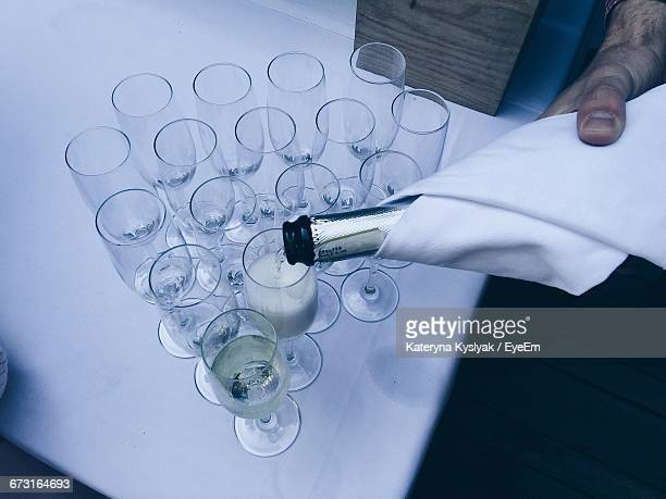 Cropped Image Of Hand Pouring Champagne In Flute