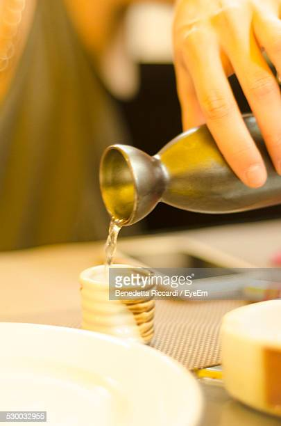 Cropped Image Of Hand Pouring Hot Sake From Traditional Flask