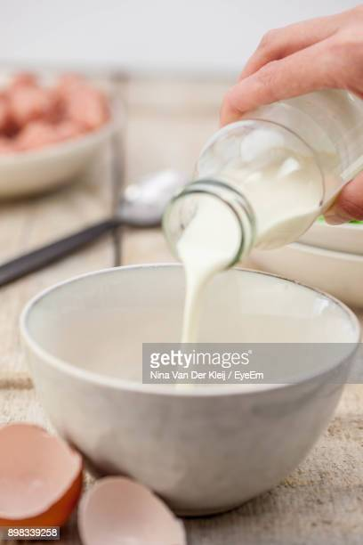 Cropped Image Of Hand Pouring Milk In Bowl