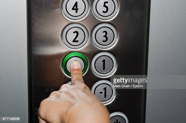 cropped image of hand pressing button in elevator - push button stock pictures, royalty-free photos & images