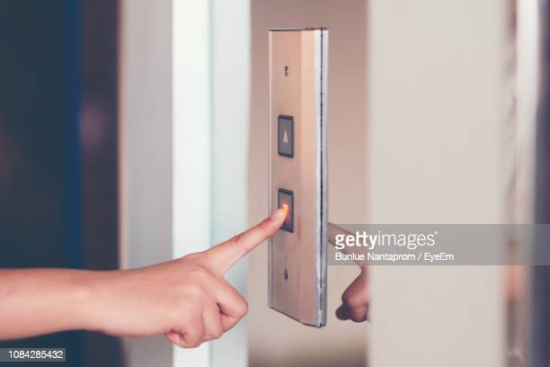 cropped image of hand pushing button of elevator - push button stock pictures, royalty-free photos & images