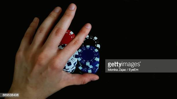 Cropped Image Of Hand Pushing Gambling Chips Over Black Background