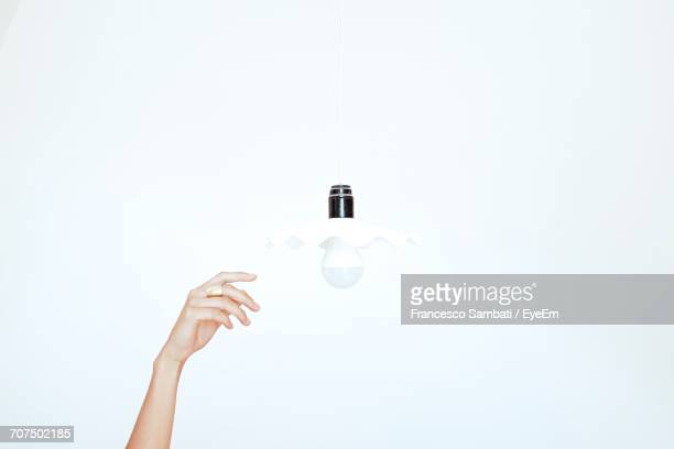 Cropped Image Of Hand Reaching For Pendant Light Against White Background