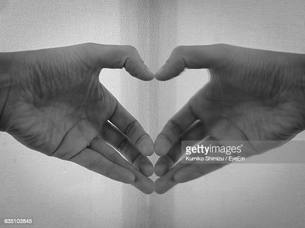 Cropped Image Of Hand Reflecting In Mirror Making Heart Shape