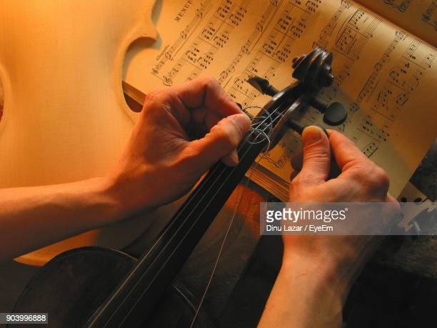 cropped image of hand repairing violin - musical instrument string stock photos and pictures