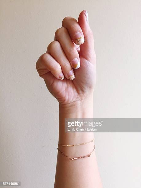 cropped image of hand showing nail paint against wall - bracelet stock pictures, royalty-free photos & images