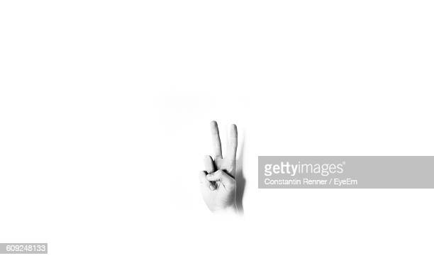 Cropped Image Of Hand Showing Peace Sign Against White Background