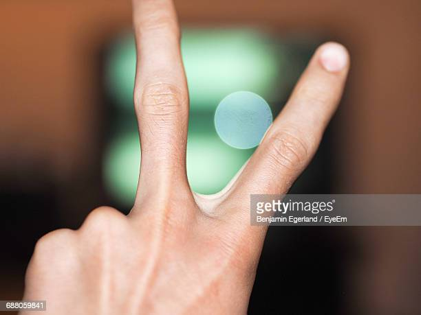 Cropped Image Of Hand Showing Peace Sign