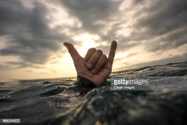 Cropped image of hand showing shaka sign in sea